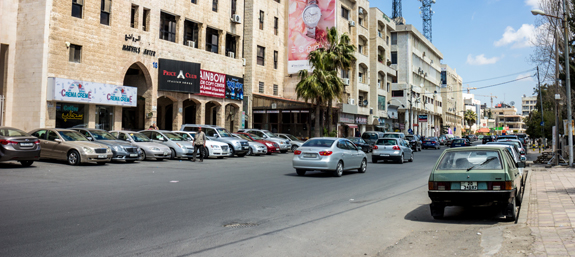 A typical street in Amman with white washed buildings and some cool old cars