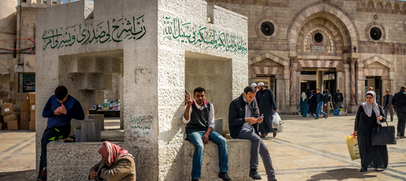 Locals sit outside one of the many Mosques in Amman