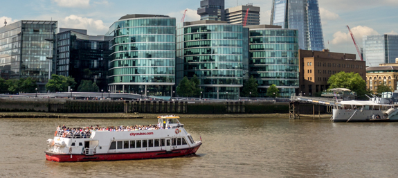A boat crosses the Thames with the Shard looming in the background